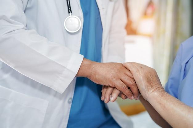 手を触れる医師愛を持つアジアの高齢者や高齢者の老婦人女性患者