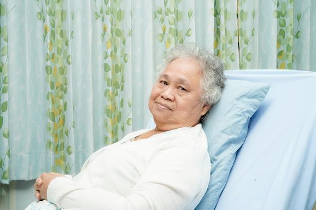 アジアの高齢者または高齢者の老婦人女性患者がベッドの上に座って