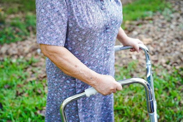 アジアの高齢者や高齢者の老婦人女性患者が公園でウォーカーと歩く
