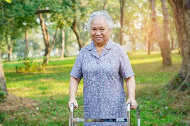 アジアの女性の女性患者が公園でウォーカーと歩く