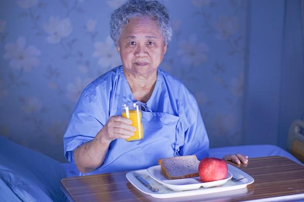 アジアの年配の女性患者の病院で朝食を食べる