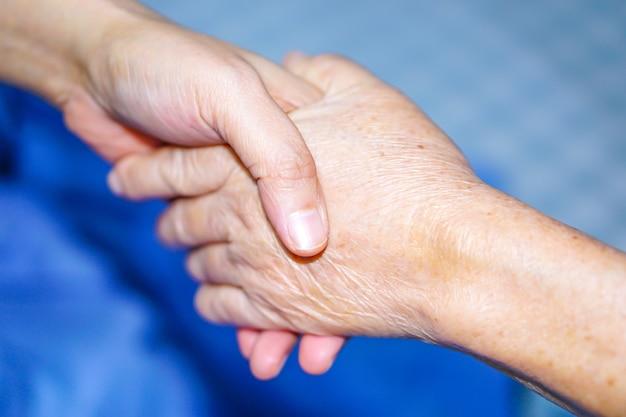 手を持つアジアの高齢者または年配の老人の愛の患者