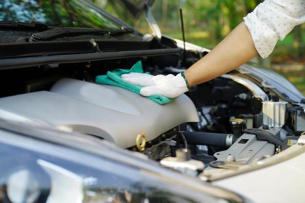 休日に屋外緑色のマイクロファイバー布で車を掃除します。