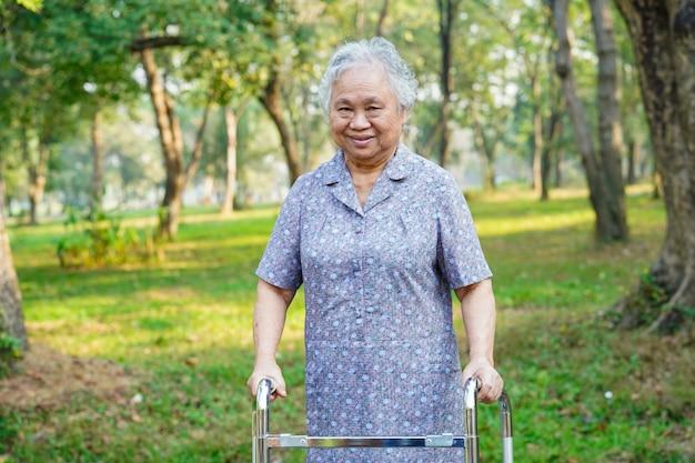 アジアの年配の女性患者は公園で散歩と歩きます。