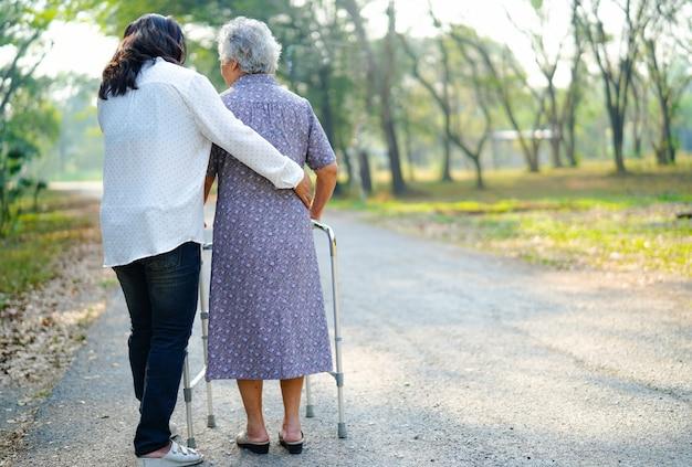 アジアの年配の女性が公園で歩きながらウォーカーを使うのを手伝ってください。