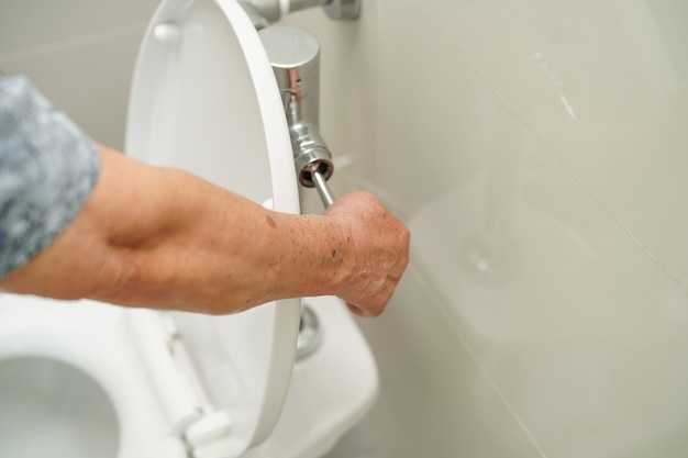 アジアのシニア女性患者プレスは使用前後に洗浄するためにトイレをフラッシュします。