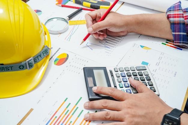 建築家またはエンジニアは、オフィスでグラフを使用してプロジェクト会計を作業します。