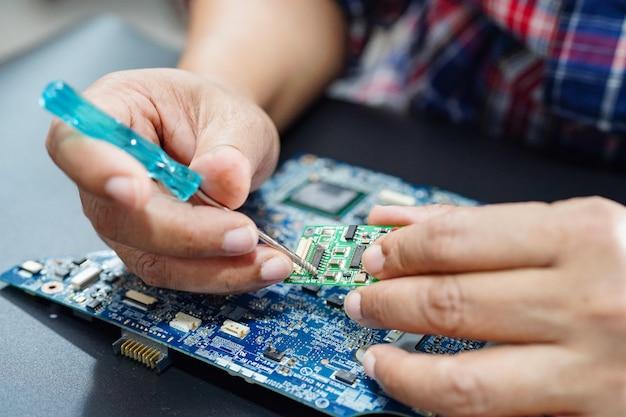 マイクロ回路のメインボードコンピューターを修理する技術者。
