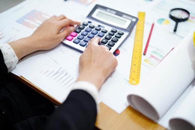 Калькулятор прессы бухгалтерии на бумаге диаграммы для работая проекта в современном офисе.