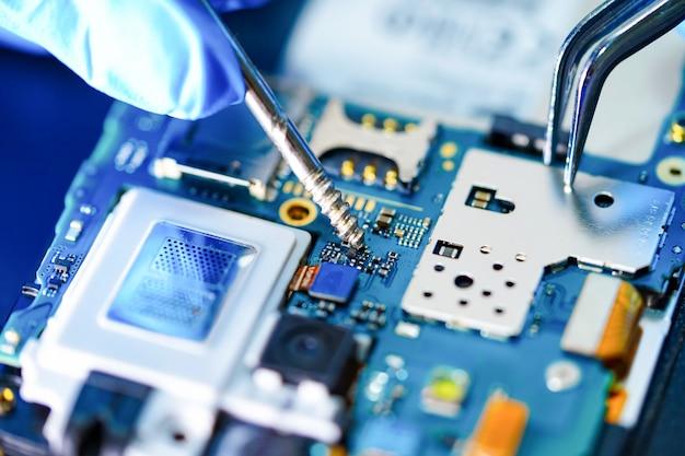 アジアの技術者がスマートフォンを修復します。