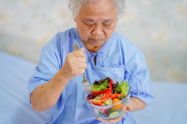 アジアのシニアまたは高齢者の老婦人女性患者の朝食の健康食品を食べる