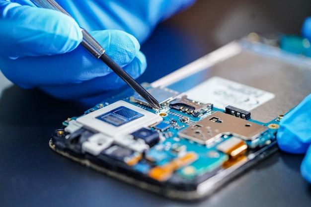 Техник ремонтирует микросхему основной платы смартфона