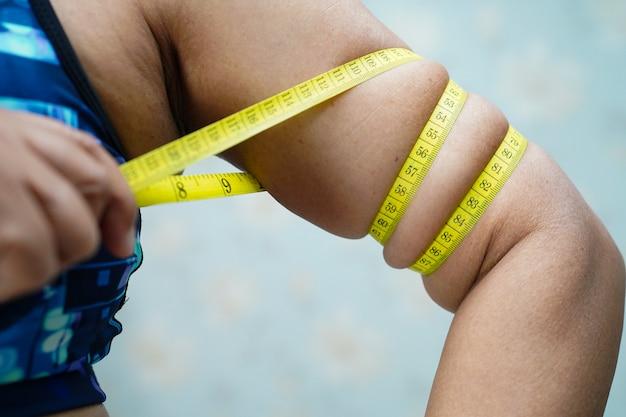 アジアの女性の女性は、測定テープによって腹体脂肪を示しています。