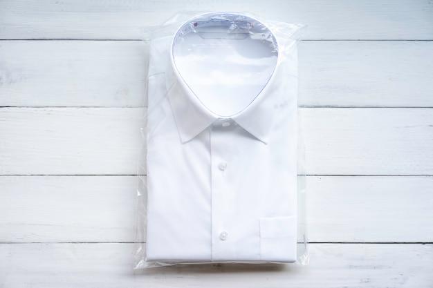 白のプラスチックパッケージで折るカジュアルな白いフォーマルなシャツ