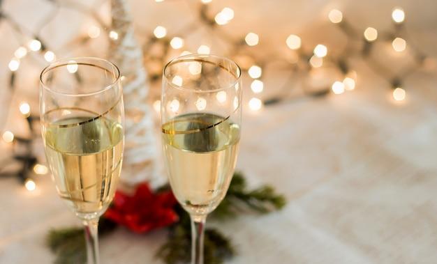 クリスマスライトゴールデン背景とシャンパンの詳細と眼鏡