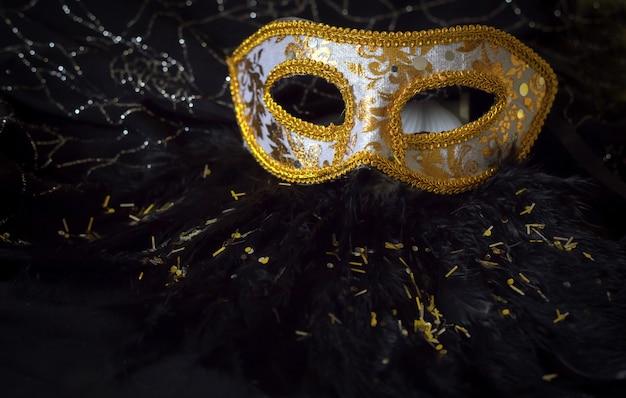 輝きと黒い羽の背景を持つ光沢のあるエレガントな白と金色のマスク