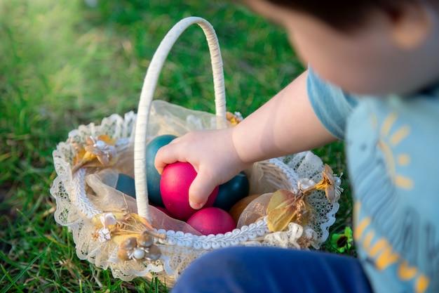 Ребенок держит пасхальные яйца, которые он нашел в корзине на траве