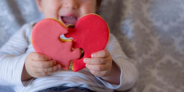 Ребенок улыбается и держит в форме сердца деталь печенья