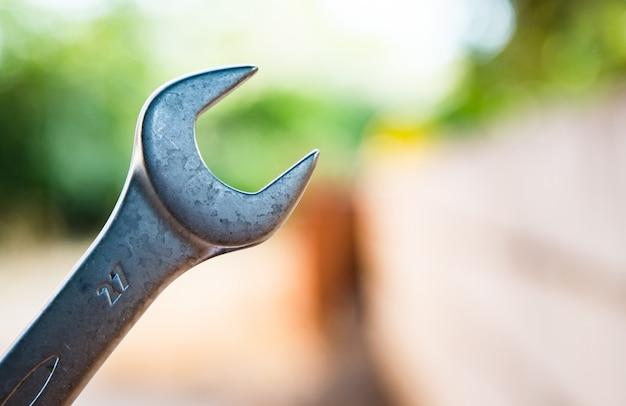 Деталь металлический гаечный ключ с размытым фоном природы и кирпичной стены
