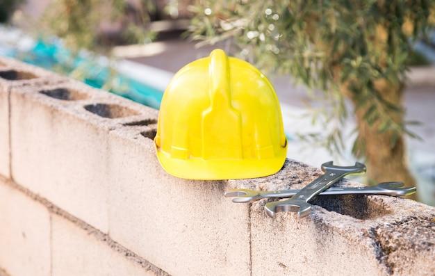 庭の半分の壁に黄色のヘルメットと金属レンチの詳細