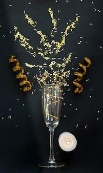 Черный и золотой бокал для шампанского и горящая свеча и конфетти