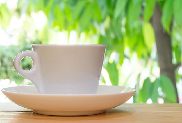 Белая кружка кофе на деревянном фоне в саду.