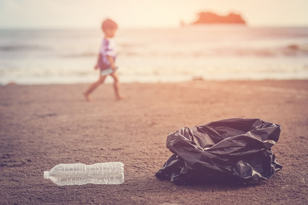 太陽の光を背景にビーチにゴミを集める/海が大好き