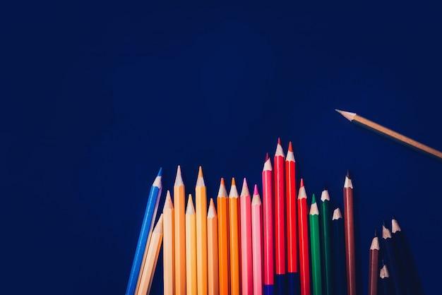 Разноцветные карандаши, изолированные на синем фоне. закройте несколько цветов.
