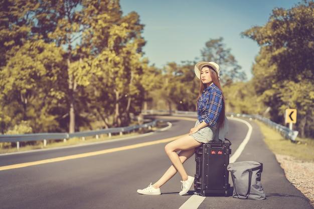 Женщина ждет машину на обочине дороги с дорожной сумкой