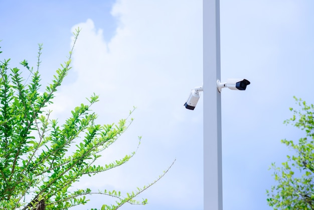 クローズドサーキットカメラは、青空の背景を持つポールに取り付けられています。