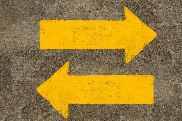 生活の方向として道路上の黄色のトラフィックの矢印記号