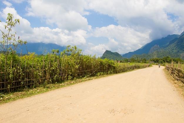 ヴァンヴィエンラオスの道路とコテージと緑の棚田