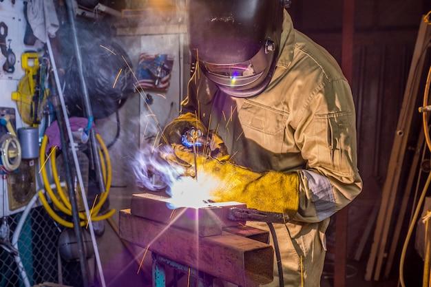 溶接機は工場で金属部品を溶接しています。工業用の保護ユニフォームとマスク溶接金属パイプの溶接機