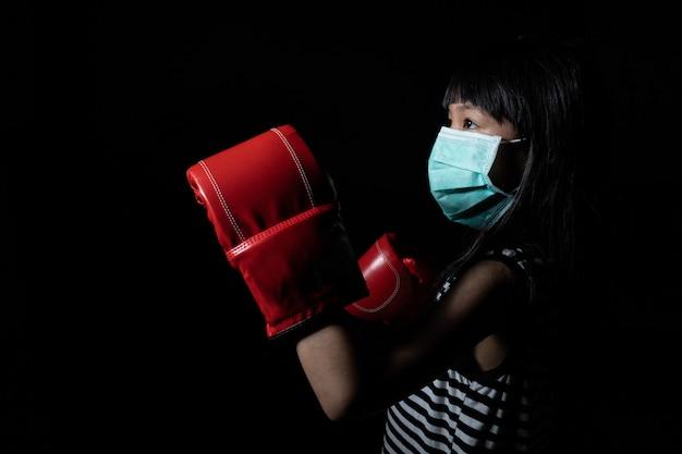 Азиатские девушки носят маски для защиты от вирусов и боксерские перчатки, которые символизируют борьбу с вирусами как коронавирус