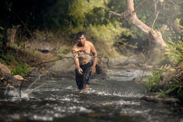 漁師は、地方の小川で釣りをするために網を投げかけています。