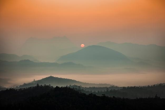 山は朝日で覆われた霧で覆われています。
