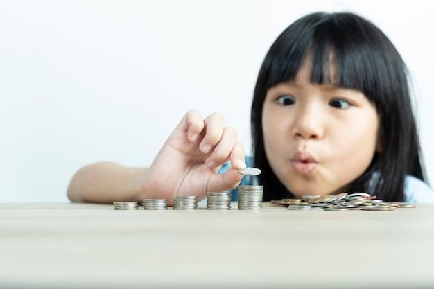 白い壁でお金を節約するために、アジアの女の子はコインを整理して数えます。