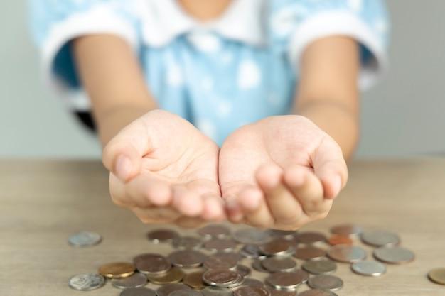 落下するコインを支えるために女の子の手が突き出ていました。コピースペースのビジネスコンセプトです。