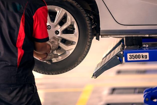 整備士は、タイヤセンターを使用する人のために車のタイヤを交換しています。