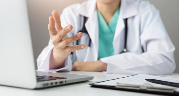 Азиатский доктор обсуждая и советуя с с пациентом о его симптомах информации с портативным компьютером на больнице. врач или специалист, делая онлайн-конференцию в белой медицинской комнате.