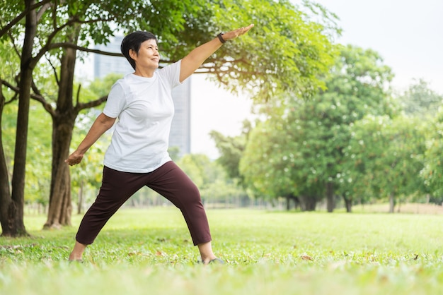 Расслабленная азиатская старшая женщина в белой ткани делая протягивающ разминку ее оружия на парке. улыбающаяся пожилая тайская женщина наслаждается тренируясь на природе снаружи