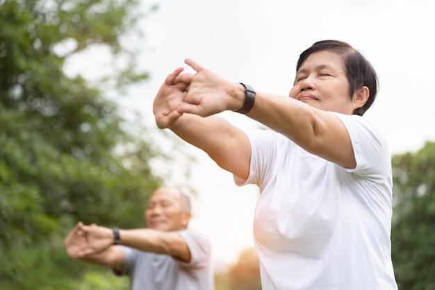 高齢者が公園で運動する前に手、腕を伸ばしています。朝の屋外でのトレーニングを楽しんで幸せなアジアシニアカップル。