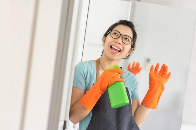 白い部屋でマイクの歌うような緑のクリーナースプレーボトルをもつ少女。エプロンとオレンジ色のゴム手袋をはめた青いシャツを着てアジアの女性を笑顔で家の掃除を準備します。