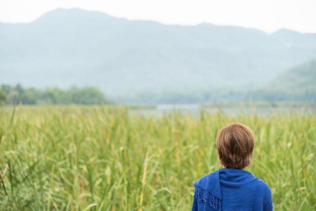 Азиатская женщина, глядя на поле и горы.
