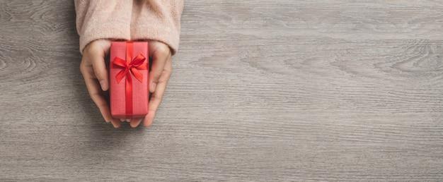 女性の手の平面図は、小さな赤いギフトボックスを持っています。