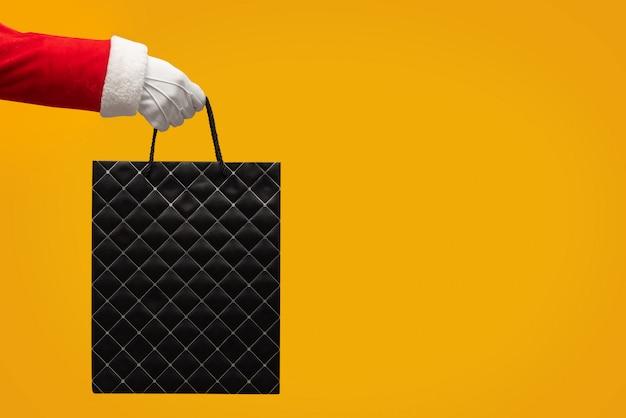 Рука санта клауса держа черную хозяйственную сумку на изолированном желтом цвете.
