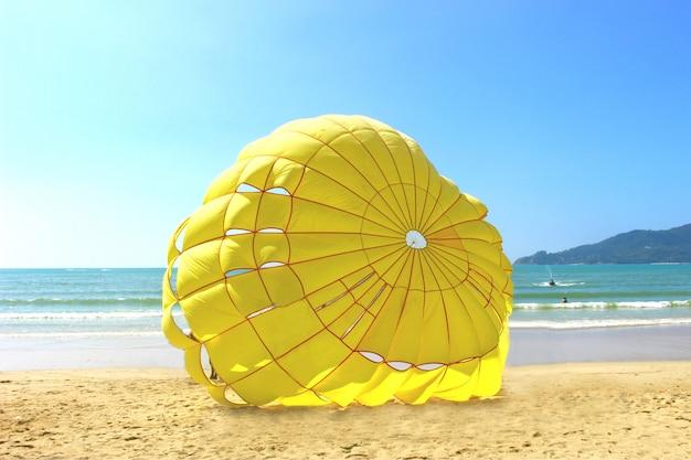 晴れた日の午後のビーチでの黄色のパラシュート