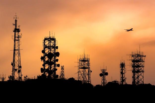 Силуэт башни связи на горе с самолетом выше