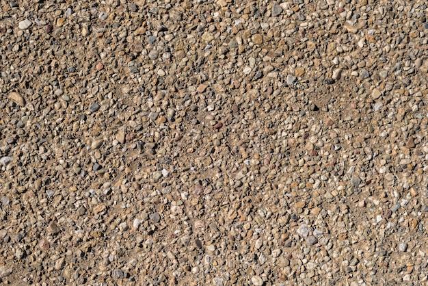茶色の自然な砂利の石は、地面のテクスチャの背景にサイズをランダム化