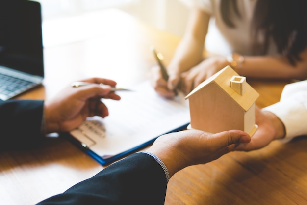 新しい家の鍵と顧客とのハンドシェイクを提供するブローカー
